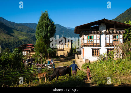 Woman and child with cattle in front of traditional farm houses in Nabji Village in southern Bhutan - Stock Image