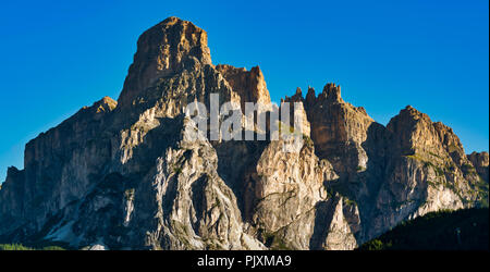 the summit of Sassongher with the first lights of the Sun on a clear summer morning, Alta Badia - Trentino-Alto Adige, Italy - Stock Image