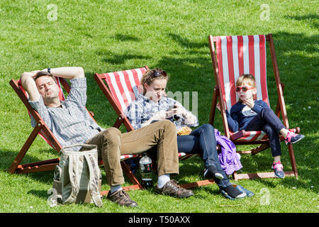 Bath, Somerset, UK. 19th Apr, 2019. With many parts of the UK expecting to experience very warm weather over the easter bank holiday period a family are pictured enjoying the warm sunshine in Parade Gardens. Credit: lynchpics/Alamy Live News - Stock Image