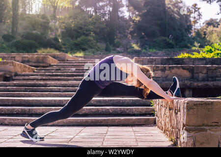 beautiful young woman doing stretching exercise on the stairs of the park, morning workout outdoors, sports and healthy lifestyle - Stock Image
