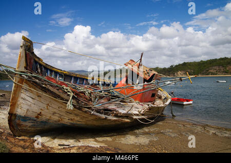 Old fishing boat turned on a side, wrecked and rotting on a rocky shore by the Mira River bank. Bright blue clouded - Stock Image