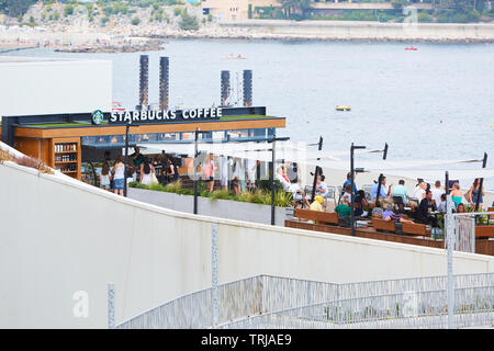 MONTE CARLO, MONACO - AUGUST 19, 2016: Starbucks Coffee cafe terrace with people in summer in Monte Carlo, Monaco. - Stock Image