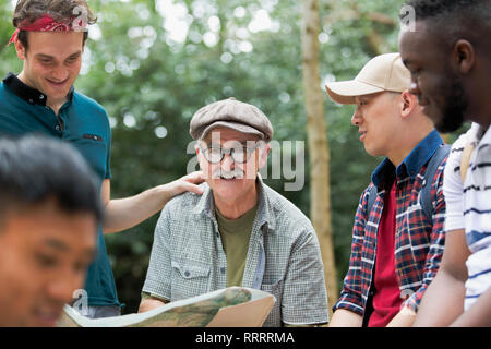 Portrait smiling man with map on hike with friends - Stock Image