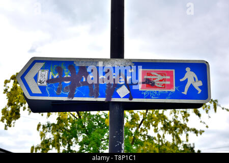 Modern British rail sign vandalized with tagging and graffiti - Stock Image