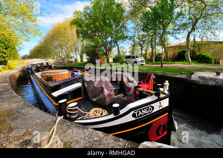 Traditional french barge in a lock on a sunny spring day on the Canal Du Midi  with the trees in full bloom, South of France - Stock Image