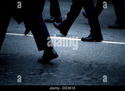 Many black colored legs and shoes marching on a street with a white line. - Stock Image