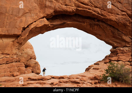 Visitor taking a picture of North Window Arch in Arches National Park, Utah, USA. - Stock Image