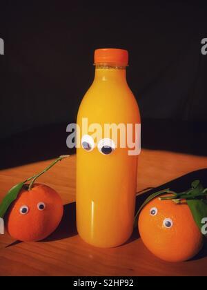 Creative fun food : organic oranges with google eyes next to a googly eyed bottle of freshly squeezed orange juice - Stock Image