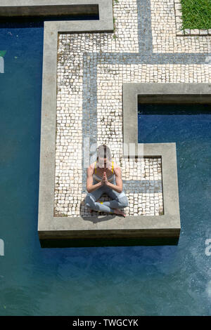 woman meditating practicing yoga outside by a water garden. top view. - Stock Image