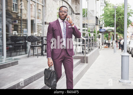 Portrait of a young beautiful African American businessman with a briefcase. Business meeting. - Stock Image