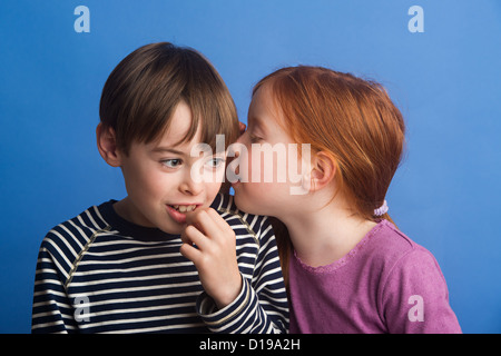 Girl aged 6 on a blue background whispering in ear of boy, 8. Boy listens with interest. - Stock Image