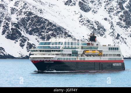 Hurtigruten Coastal Express cruise MS Trollfjord ship passes Havøya Island in Finnmark County, northern Norway. - Stock Image