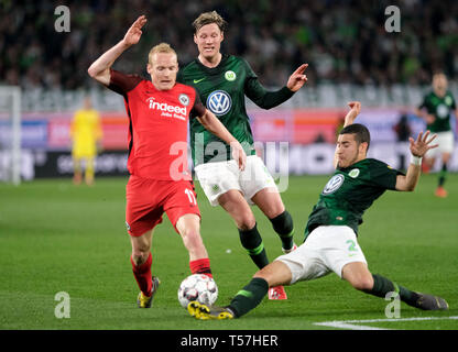 Wolfsburg, Germany. 22nd Apr, 2019. Soccer: Bundesliga, 30th matchday: VfL Wolfsburg - Eintracht Frankfurt in the Volkswagen Arena. Wolfsburg's Wout Weghorst (M) and William (r) and Frankfurt's Sebastian Rode fight for the ball. Credit: Peter Steffen/dpa - IMPORTANT NOTE: In accordance with the requirements of the DFL Deutsche Fußball Liga or the DFB Deutscher Fußball-Bund, it is prohibited to use or have used photographs taken in the stadium and/or the match in the form of sequence images and/or video-like photo sequences./dpa/Alamy Live News - Stock Image