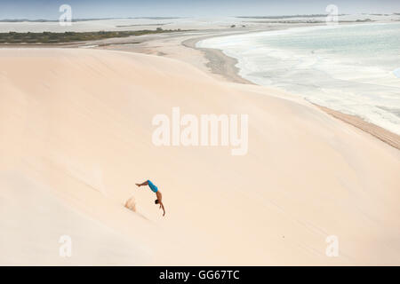 geography / travel, Brazil, Ceara, Jericoacoara, local boy somersaulting down a dune next to the beach, South America - Stock Image