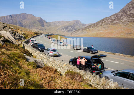 Cars parked on roadside and pavement along A5 road in Ogwen Valley on busy Easter weekend in Snowdonia National Park. Ogwen north Wales UK Britain - Stock Image