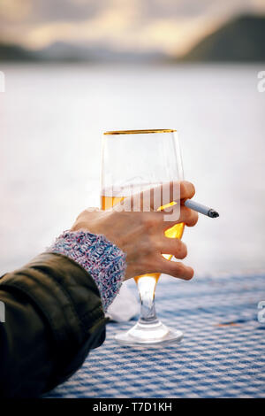 Close up hand of a woman holding a glass of beer and a cigarette with blurred sea, sky and island background at sunset. - Stock Image