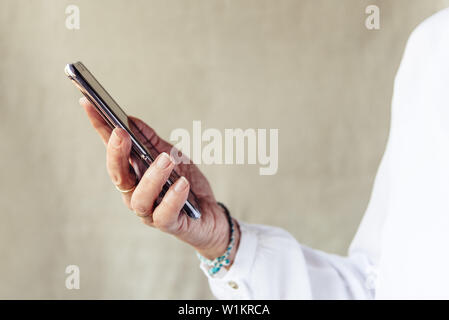 Close up of woman hand with smartphone.  Business, technology, communication, leisure and people concept - Stock Image