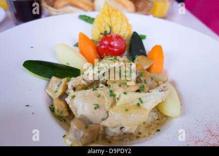 Casseroled chicken breast with turned vegetables - Stock Image