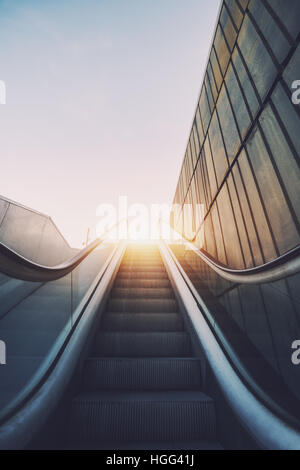Outdoor city escalator stairway, under evening sun, with tiled rusty concrete wall on the right, wide view from - Stock Image