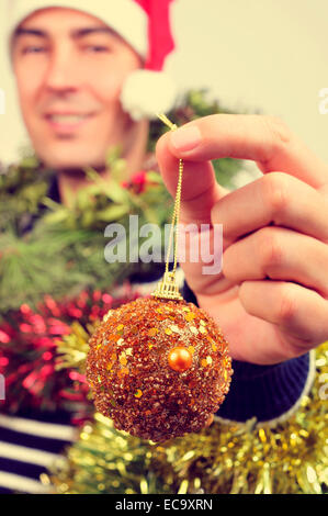 a young man wearing a santa hat covered with christmas ornaments and holding a bauble in his hand - Stock Image