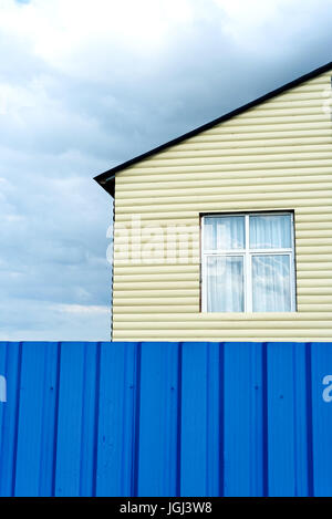 Metal clad house exterior in cream with a curtained window and a blue metal fence - Stock Image