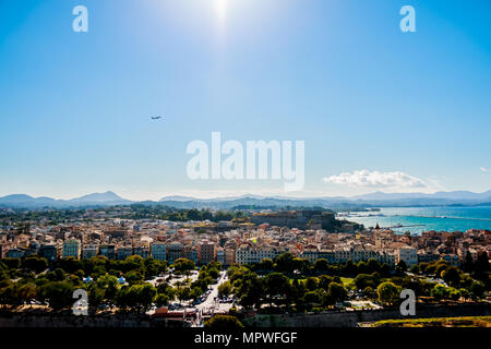 corfu or kerkira houses and island view from top point of old fortress ,ioania sea , greece vacation. Amazing view to the city and plane in blue clear sky. - Stock Image