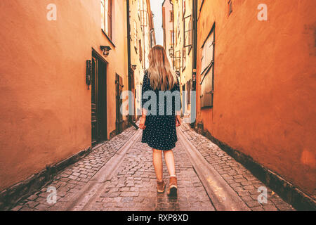 Young woman walking alone in Stockholm  travel lifestyle summer vacations in Sweden old city cobblestone street - Stock Image