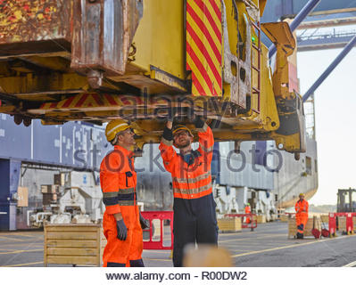 Dock workers repairing crane and loader at port - Stock Image