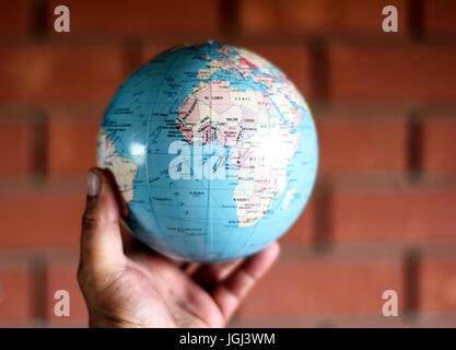 Globe map of planet earth held by a human hand against a brick wall - Stock Image