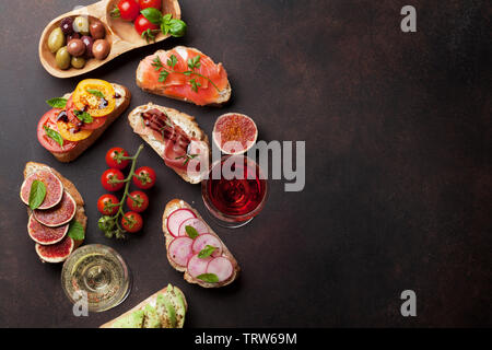 Brushetta or traditional spanish tapas. Appetizers italian antipasti snacks set with rose and white wine. Top view and flat lay with space for your te - Stock Image