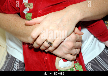 mothers hand holding baby red romper suit caucasian love protection security safe - Stock Image