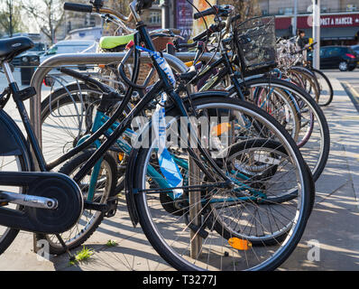 Line of bicycles in a bike rack on a busy London street. - Stock Image