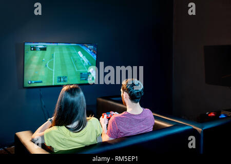 Young couple playing football game with gaming console sitting on the couch at the playing club, back view with tv screen - Stock Image