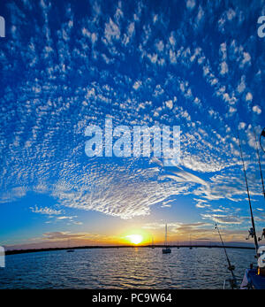 A spectacular inspirational brightly coloured atmospheric cloudy sky cloudscape featuring a Altocumulus cloud formation in a mid blue sky. New South W - Stock Image