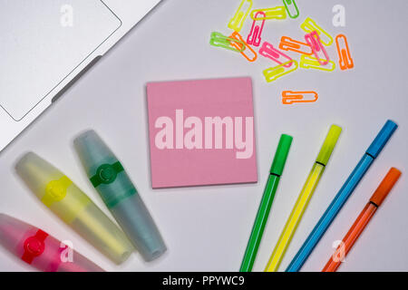 Office desk table with sticky note, pens, markers, computer. Top view with copy space. - Stock Image