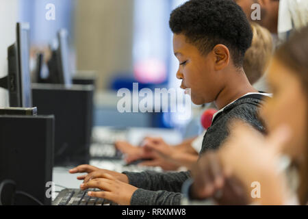 Focused junior high boy student using computer in computer lab - Stock Image