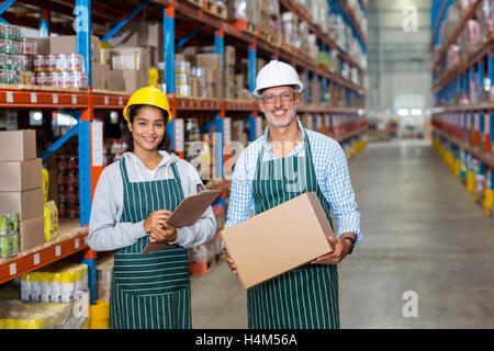Portrait of warehouse workers standing with clipboard and cardboard boxes - Stock Image