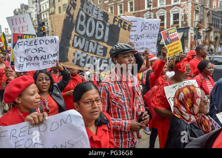London, UK. 23rd August 2018. Hundreds of Ugandans, mainly dressed in red, march from the Ugandan Embassy to Downing St to say that President Museveni must go. They accuse him of being a dictator, and called for and end to the killing of opposition politicians and for  the release of those imprisoned, including business man, MP and singer Bobby Wine (Robert Kyagulanyi Ssentamu), and an end to land grabbing. Credit: Peter Marshall/Alamy Live News - Stock Image