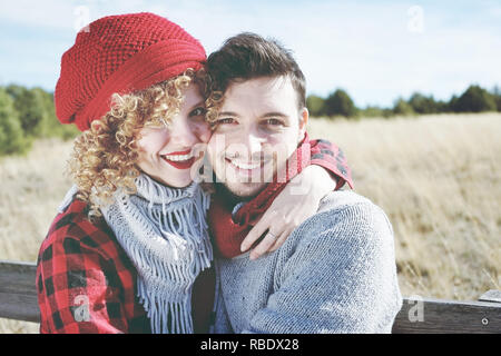 Romantic young couple of lovers look at the camera while smiling in love sitting in a outdoor wooden bench with nature as background - Stock Image