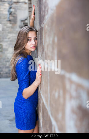 Cheerful female is playfully posing in blue dress near wall of building outdoor. - Stock Image