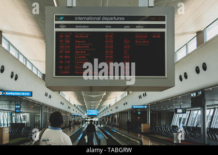 Man traveler passenger looks at flight schedule timetable board screen at terminal, O.R. Tambo International Airport, Johannesburg, South Africa - Stock Image