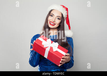 Pretty woman in braces holding Christmas or New Year gift and smiling - Stock Image