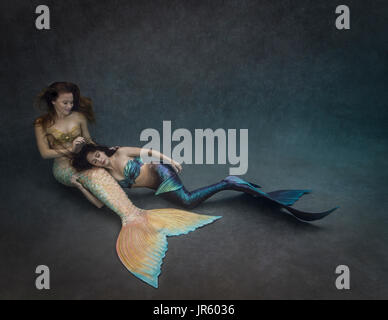 Two young mermaids relaxing together - Stock Image