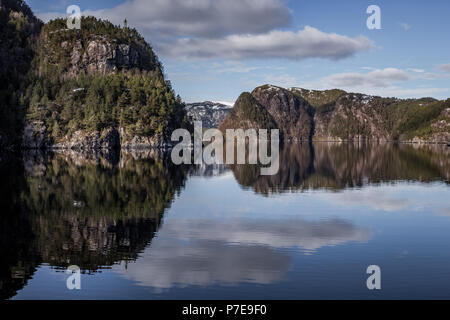 Calm sea in the Norwegian Fjord Osterfjorden, creating stunning reflections from the Bergen to Mostraumen cruise. - Stock Image