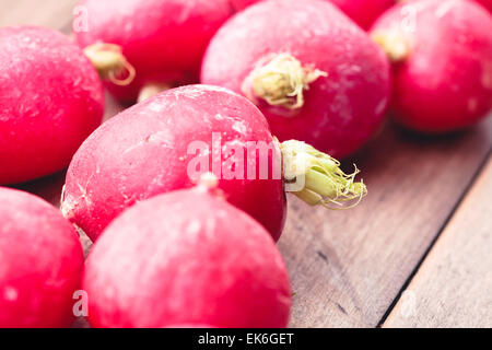 Fresh raw radishes on a wooden surface - Stock Image