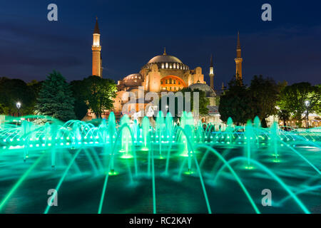 The Sultan Ahmad Maydan water fountain lit up with the Hagia Sophia museum in background at dusk, Istanbul, Turkey - Stock Image