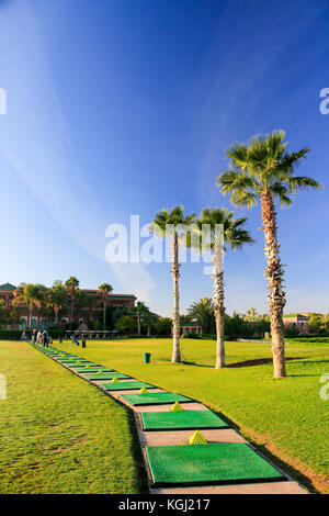 Open air golf driving range in Morocco with mats, piles of balls, palm trees and blue sky. Portrait. No people. - Stock Image