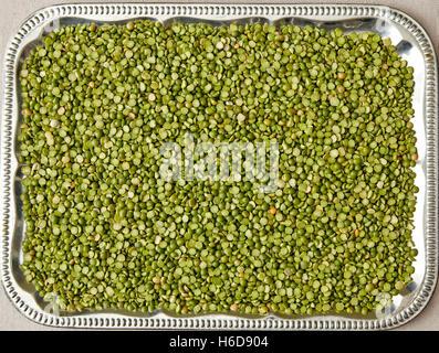 uncooked split peas spread onto a tray - Stock Image
