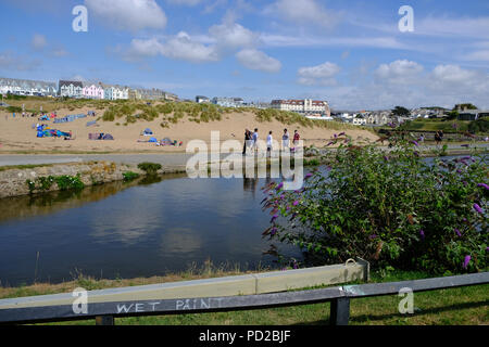 Bude, Cornwall, UK. UK Weather. Holidaymakers enjoy the hot weather, walking along the Bude canal with Summerleaze beach in the background - Stock Image