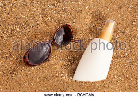 Summer Holidays - Sun glasses and sun cream on a sand background - Stock Image